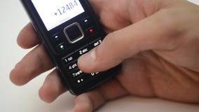 Manos del número del dial de la persona en el teléfono celular En el fondo blanco almacen de metraje de vídeo