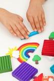 Manos del niño con el modelado de la arcilla Foto de archivo libre de regalías