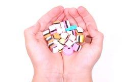 Manos del niño con los caramelos Foto de archivo libre de regalías