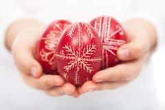 Manos del niño con los huevos de Pascua tradicionales Imagen de archivo