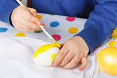 Manos del niño pequeño que pintan los huevos coloridos para la caza de Pascua Fotos de archivo