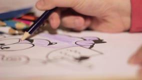 Manos del niño del primer con el lápiz el niño dibuja con el lápiz coloreado en el papel almacen de metraje de vídeo