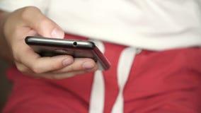 Manos del niño del primer con un teléfono muchacho que usa el teléfono almacen de metraje de vídeo