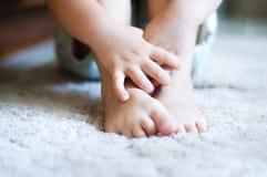 Manos del niño que abrazan pies descubiertos Foto de archivo libre de regalías