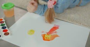 Manos del niño que crean la imagen con las pinturas coloridas almacen de metraje de vídeo