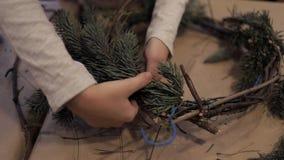 Manos del niño que enrollan encima de las ramas de árbol de navidad que hacen una guirnalda