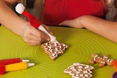 Manos del niño que hacen las galletas de la Navidad - primer Foto de archivo