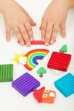 Manos del niño que juegan con la arcilla de modelado Foto de archivo