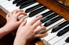 Manos del niño que juegan el piano Fotos de archivo