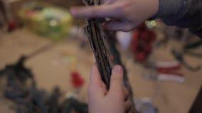Manos del niño que refuerzan las barras de madera con un alambre que hace la guirnalda de la Navidad