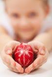 Manos del niño que sostienen el huevo de Pascua adornado tradicional Imagen de archivo