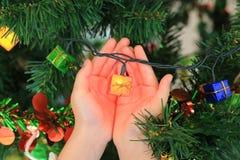 Manos del niño que sostienen el regalo mágico de la Navidad decorativo Concepto de la Feliz Navidad y de la Feliz Año Nuevo imagen de archivo