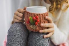 Manos del niño que sostienen la taza blanca en cubierta hecha punto invierno Imágenes de archivo libres de regalías