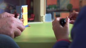 Manos del niño sincero y del papá que juegan con las marionetas cercanas encima de SF almacen de metraje de vídeo