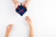 Manos del niño y del adulto que dan y que reciben un presente Fotos de archivo libres de regalías
