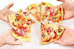 Manos del niño y del adulto con los pedazos de pizza Fotografía de archivo