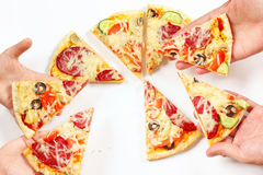 Manos del niño y del adulto con los pedazos de pizza sabrosa Imágenes de archivo libres de regalías