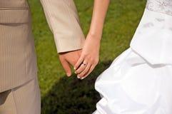Manos del novio de la novia Foto de archivo libre de regalías
