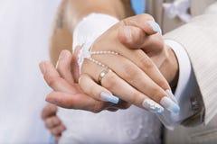 Manos del novio y de la novia. Foto de archivo