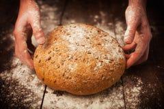 Manos del panadero con pan fresco en la tabla Fotografía de archivo