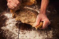 Manos del panadero con pan fresco en la tabla Foto de archivo libre de regalías