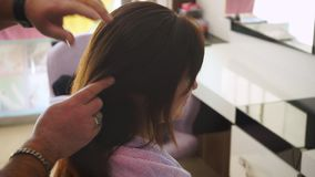 Manos del pelo liso del peluquero en la cabeza de la chica joven almacen de video