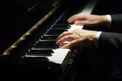 Manos del pianista del músico profesional en llaves del piano de un piano clásico fotografía de archivo