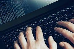 Manos del pirata informático en el trabajo sobre un ordenador portátil Primera opinión de la persona Foto de archivo libre de regalías