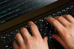 Manos del pirata informático en el trabajo sobre un ordenador portátil Primera opinión de la persona Fotos de archivo libres de regalías