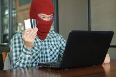 Manos del pirata informático enmascarado que lleva un pasamontañas que sostiene la tarjeta de crédito entre el robo de datos del  foto de archivo