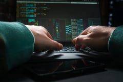 Manos del pirata informático, primera opinión de la persona, en el trabajo con el interfaz y la tarjeta de crédito robada fotos de archivo