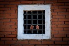 Manos del preso detrás de las barras, color Imagenes de archivo