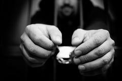 Manos del preso en un cierre de acero del enrejado para arriba Imagen de archivo libre de regalías
