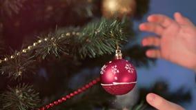 Manos del primer del árbol de navidad adornado bebé que cuelga la bola roja grande en brunch metrajes