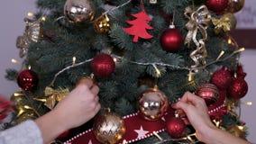 Manos del primer de la gente que cuelga los juguetes de la Navidad en el árbol de navidad almacen de video