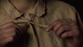 Manos del primer de la mujer joven que ajustan el arco en la ropa metrajes