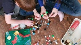 Manos del primer de los modelos de la molécula del edificio de la mamá y del hijo del sistema plástico coloreado de la construcci almacen de metraje de vídeo