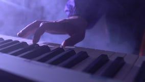 Manos del primer del músico que juega los teclados metrajes
