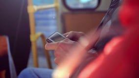 Manos del primer en el hombre del autobús que usa su teléfono celular almacen de metraje de vídeo