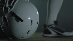 Manos del primer del jugador de fútbol americano en los guantes que mienten en su casco antes del cierre del juego para arriba Co almacen de metraje de vídeo