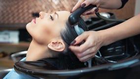 Manos del primer del pelo que se lava del peluquero profesional al cliente de la mujer en el salón de belleza metrajes