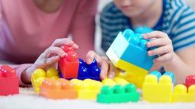 Manos del primer del psicólogo y del niño pequeño del niño femenino que juegan con los cubos coloreados durante la prueba almacen de metraje de vídeo