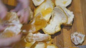 Manos del primer que pelan la fruta anaranjada en tablero de la cocina almacen de video