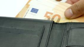 Manos del primer que ponen billetes de banco euro del dinero en la cantidad 4k de la cartera almacen de video