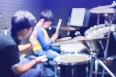 Manos del profesor con los palillos de madera que dirige al muchacho en tambor que aprende tutorial en el estudio de grabaci?n en foto de archivo libre de regalías