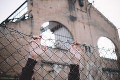 Manos del refugiado que guardan la malla de la cerca del metal Fotos de archivo