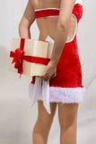 Manos del regalo de Navidad de ocultación de la muchacha Imagen de archivo