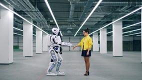Manos del robot blanco y de un tacto de la mujer, saludándose almacen de metraje de vídeo