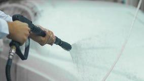 Manos del rociador que se sostiene masculino, cubriendo el auto costoso con espuma, lavado del coche almacen de metraje de vídeo