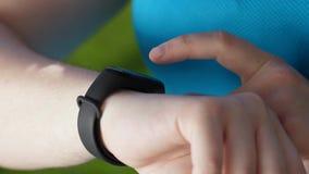 Manos del runnner gordo de la mujer usando la pulsera de la aptitud almacen de video